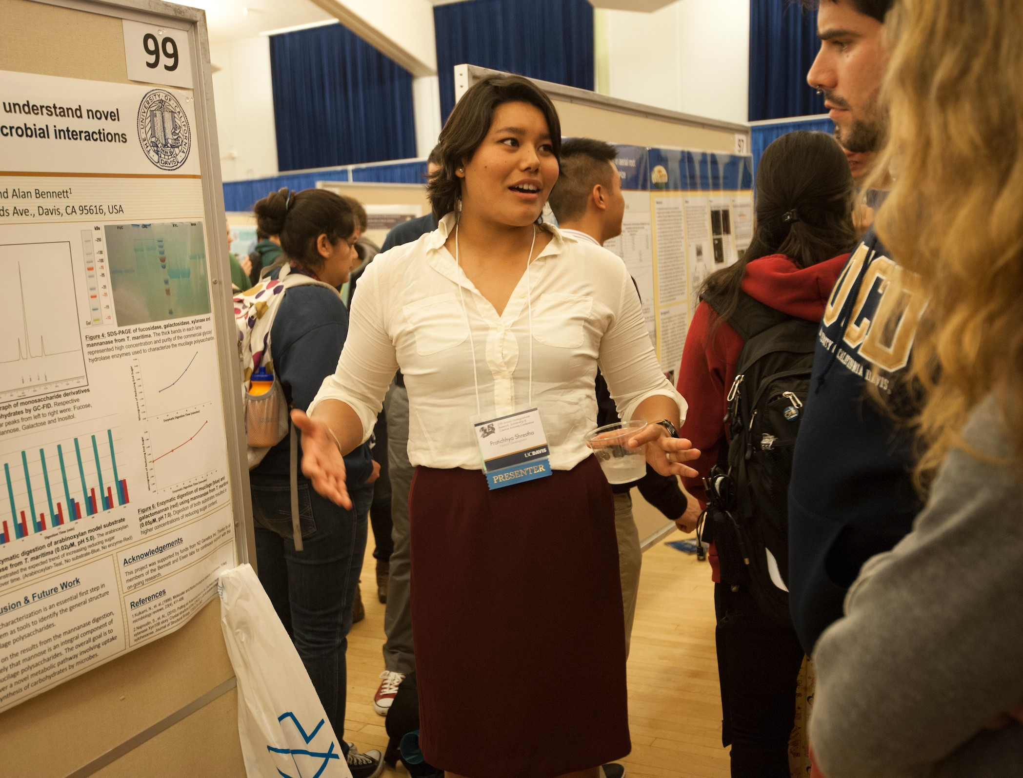 Woman talking in front of her scientific poster